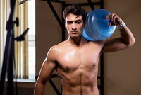 Muscular ripped man with big water bottle