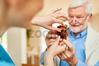 Pflegekraft und Senior halten ein Holzpuzzle