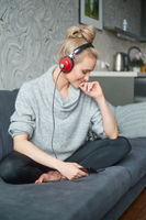Adorable middle aged blond woman sitting on sofa in her home and listen to the music
