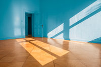 bright empty apartment room with blue walls and wooden floor