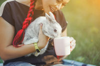 Kind Asian Gives Water to Her Little Fluffy Bunny