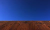 old brown oak wooden table on the blue sky clouds background, wood table