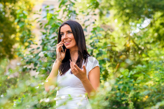 A cheerful young woman in a Park talking on a phone