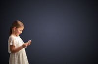 Cute little girl using tablet with dark background