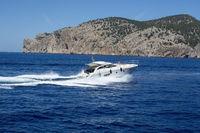 Motor boat speeding woman on deck making foamy waves