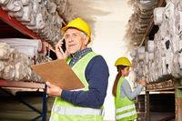 Senior Lagerarbeiter im Warenlager telefoniert