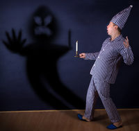 The man in pajamas holding candle is scared from own shadow on wall.