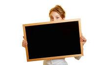 Frau versteckt sich schüchtern hinter Tafel