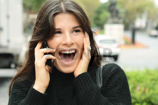 Portrait of a surprised woman talking on smart phone