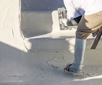 Worker Wearing Spiked Shoes Smoothing Wet Pool Plaster With Trowel