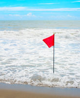Waving red flag at seashore