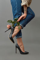 A woman's hand with a tattoo is holding a pink rose near her legs in jeans and stylish high-heeled shoes around a dark background with space for text. Photo as layout for a postcard
