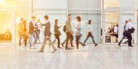 Anonyme Menschen gehen durch Halle in Büro
