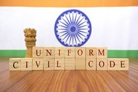 Concept of One law for all called Uniforn Civil code or UCC in Indian constitution in wooden block letters and Indian flag as a background