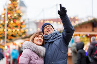 happy senior couple hugging at christmas market