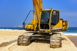 Yellow excavator cabin over sand