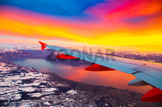 Amazing view from the airplane window during the sunset over mountains in Switzerland