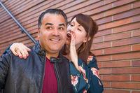 Caucasian Woman Whispering Secret to Hispanic Man
