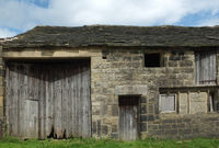 ancient abandoned stone barn in a row of rural buildings with empty windows and wooden doors with the pavement overgrown with grass