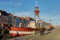 People cycling through colourful facades and restaurants on Nyhavn embankment and old ships along the Nyhavn Canal in Copenhagen, Denmark