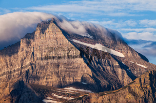 A blanket of clouds covers a mountain peak in Glacier National Park, Montana