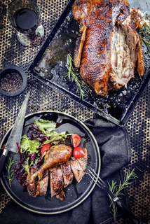 Traditional roasted Christmas duck with lettuce and tomatoes as top view on a plate