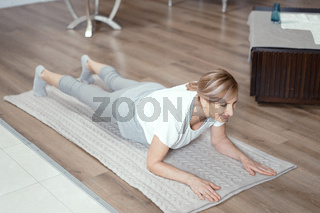 Beautiful mature woman stands in plank position