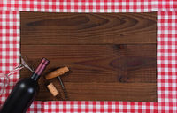 Red and white checked table runners forming a frame with a bottle of red wine