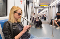 Young girl reading from mobile phone screen in metro.