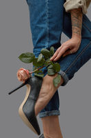 Stylish composition of beautiful female legs in jeans, black high heeled shoes and a pink rose adorning the leg around a dark background with copy space.