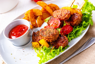 Meatballs skewers of tomato, paprika and baked potato quarters