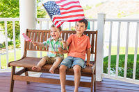 Young Mixed Race Chinese and Caucasian Brothers Playing With American Flags