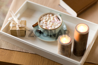 hot chocolate, christmas gift and candles on table