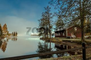 Ein rotes Schwedenhaus an einem nebligen Herbstmorgen