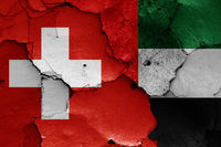flags of Switzerland and United Arab Emirates painted on cracked wall