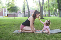 Woman exercising with her baby girl in the park