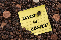 Five cent euro coin over fresh coffee roasted beans and a note with the phrase: invest in coffee