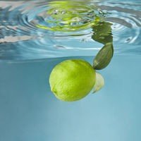 Yellow fresh lemon falling water with a splash on a blue background