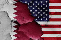 flags of Qatar and USA painted on cracked wall