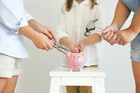 Kids with screwdriver, pliers and hammer by the pink pig piggy bank