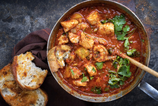 Traditional Creole cajun court bouillon with fish and seafood gumbo chowder stew as top view in a pot
