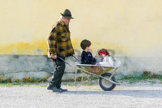 elderly man carrying children on wheelbarrow