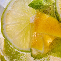 Macro background of lemonade with pieces of lemon and bubbles of air.