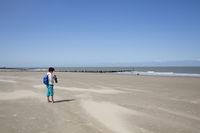 Frau an menschenleerem Sandstrand bei Cadzand