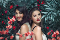 Summer two women portrait inspired by nature lifestyle. Beauty spring girls with blooming flowers wreath hairstyle on her head.