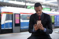 Happy young African businessman using phone at the train station