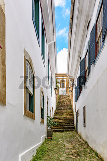 Old cobblestone street with houses in colonial style