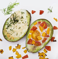 Baked avocado with eggs , cheese and vegetables on white background