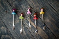 Colorful Dessert Forks with Colorful Trinket Handles on Blue