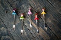 Colorful Dessert Forks with Colorful Trinket Handles on Blue